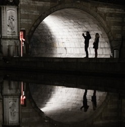 Silhouettes of unidentifiable tourists taking a picture under a bridge reflected in a canal  in Ghent, Belgium at night.