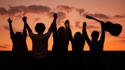 Silhouettes of unrecognizable people with guitar raising arms against cloudy sundown sky during party on rooftop