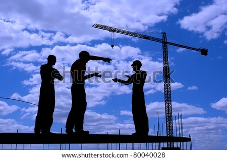 Silhouettes of workers at a construction site.