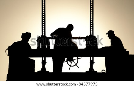 Silhouettes of workers at work in the evening
