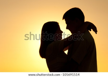 Silhouettes of young couple hugging on sunny summer day.