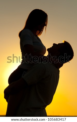 Silhouettes of young couple in love on sunny summer day.