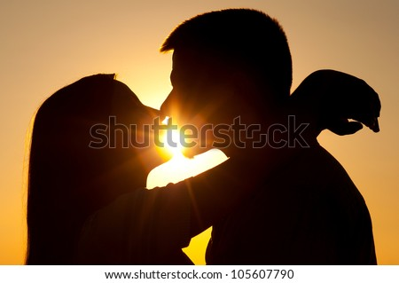 Silhouettes of young couple kissing on sunny summer day.