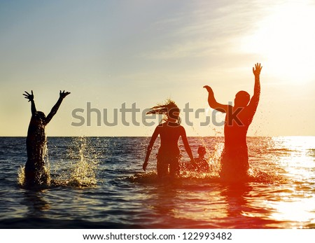Silhouettes of young group of people jumping in ocean at sunset #122993482