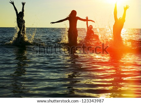 Silhouettes of young group of people jumping in ocean at sunset #123343987