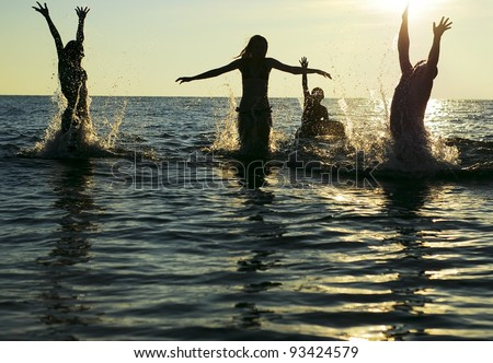 Silhouettes of young group of people jumping in ocean at sunset #93424579