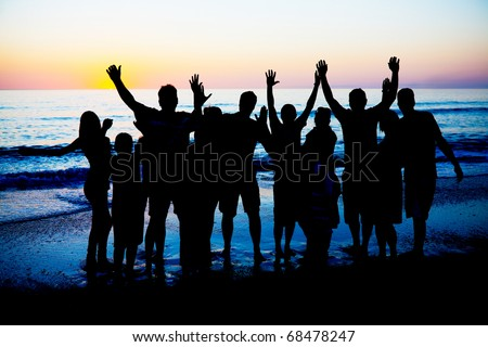 Silhouettes of young happy people enjoing sunset at the Florida beach.