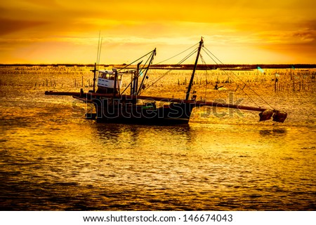 Silhouettes oftraditional fishery boat in sunset light