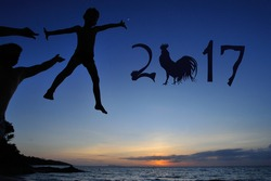 Silhouettes on the beach with a background of sunset sky: little boy jumps from dad's hands and flutters over the water. There are numbers 2017 written in the air - year of the rooster is coming up