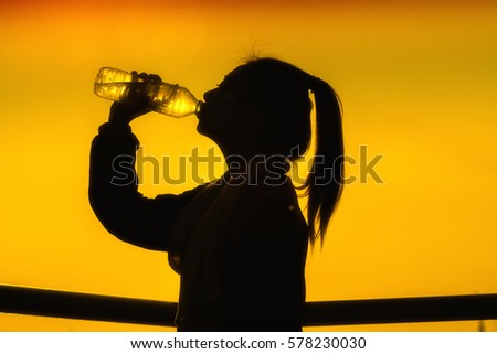 Silhouettes picture of Sporty Asian woman drinking water outdoor and soft focus