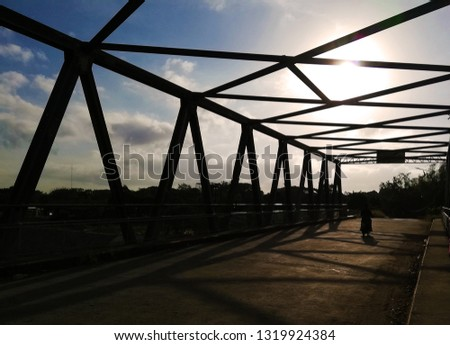 Silhoutte framework of a small bridge made with steel iron metal against a bright blue sky in broad daylight with motorcyclist driving across