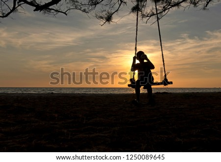 Silhoutte image of young boy drinking water on the swing,kid having fun by playing wooden swing on the beach with beautiful background of sunset over the sea. #1250089645