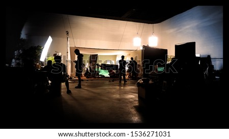 Silhoutte images of video production and lighting set for filming which movie crew team working and silhouette shadow of camera and professional equipment in big studio for commercial advertising.
