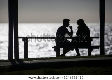 Silhoutte of a couple on a bench by the sea #1246339492