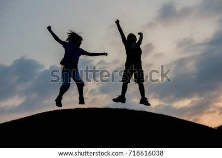 Silhoutte of two brothers enjoying the freedom #718616038
