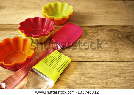 Silicone whisk, spatula, brush and cupcake liners on wooden table