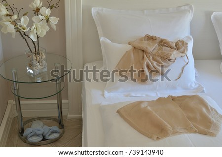 Silk babydol on a bed with pillows and bedding in an elegant bedroom