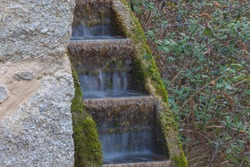 Silk effect of the water flowing into an ancient mill wheel, Grotte del Caglieron, Veneto, Italy
