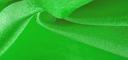 Silk fabric, green forest. Pleats in silky green fabric, close-up, full frame. Texture, background, pattern