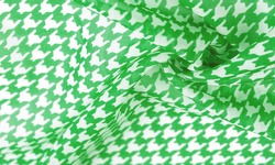 Silk fabric green pattern on a white background. A pattern on the fabric of a famous French fashion designer. Texture, background, pattern,