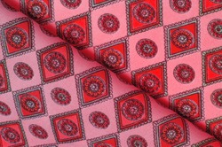 silk fabric of soft red color with a print of rhombuses, squares and medals. Tell a story and make a statement with traditional design work that has charm and value. Texture background pattern