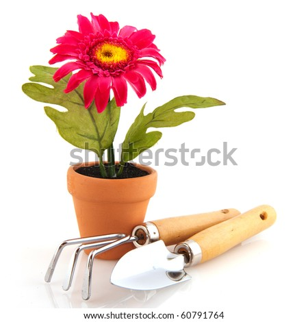 Silk pink Gerber flower in brown pot with gardening equipment
