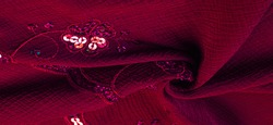 Silk red. The fabric is embellished with sequins. background, silk satin, luxurious texture, dark fabric, costume cotton material, abstract color image pattern, delicate liquid emerald velvet