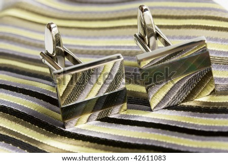 silk tie and cufflinks are posed on a nutral background