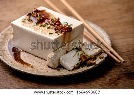 Silk tofu japanese soy cheese whole piece with chili, chive ginger and soy sauce topping on ceramic plate with chopsticks over wooden table. Сток-фото ©