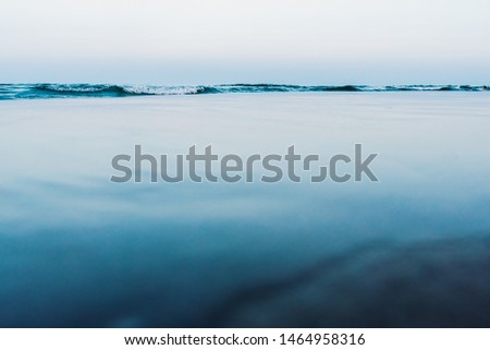 Silky calm water background with waves in the background and calm sea.