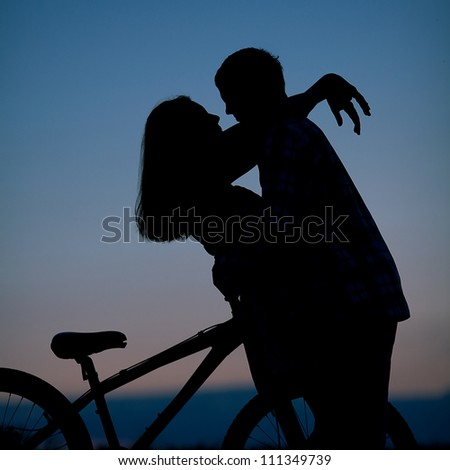 sillhouette of sweet young couple in love standing in the field. Outdoor shot