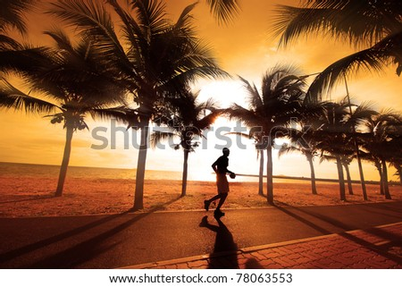 Sillouette of the man jogging. The coconut trees on the beach at sunset.