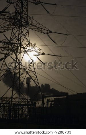 sillouettes of power pylon and chimney with smoke against bleak sun