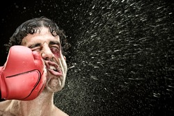 silly boxer man takes a punch in the face isolated on black.funny concept portrait