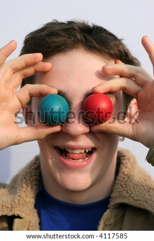Silly boy's holding in front of his eyes easter eggs