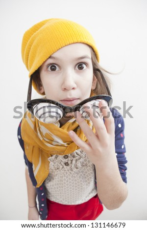 Silly little girl ten years old in yellow knitting hat with play eyeball glasses. I'm coming for you