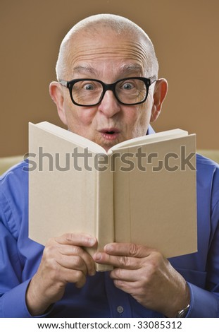 Silly senior man with glasses reading book, looking at the camera. Vertical.