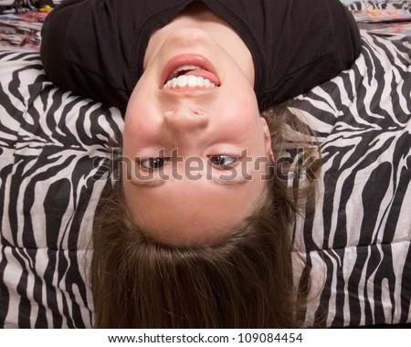 Silly upside down girl against zebra pattern