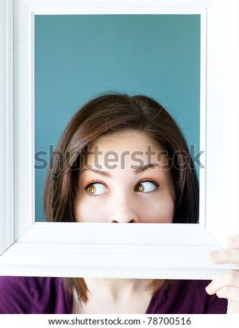 Silly woman peeking out from a white vintage picture frame.