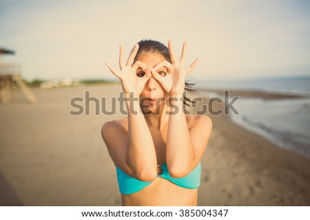 Silly young woman grimacing and having fun on the beach enjoying summer vacation holiday.Happy woman making funny face,having fun at party.Pulling funny faces.Humorous woman making someone laugh