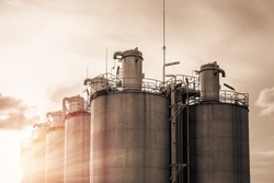 Silos in petrochemical industry, Old silo storage for plastic resins with sky sunrise