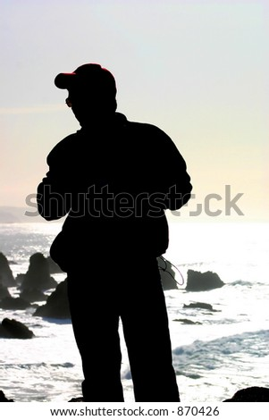 Silouette of a man standing at the edge of a cliff at Bodega Head, California. - stock photo