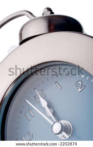 silver alarm clock with time nearly reaching midnight, midday