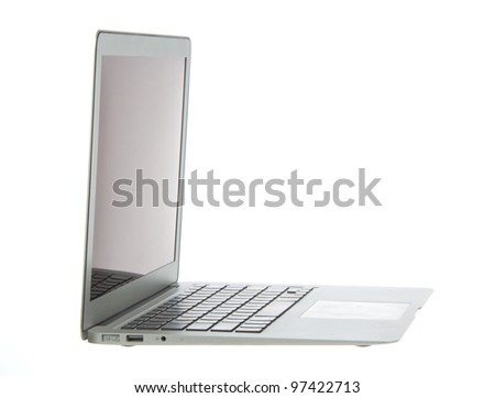 Silver aluminum laptop computer notebook side with touchpad, keyboard and open slots isolated on a white background