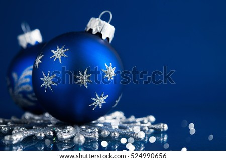 silver and blue christmas ornaments on dark blue background with space for text merry christmas
