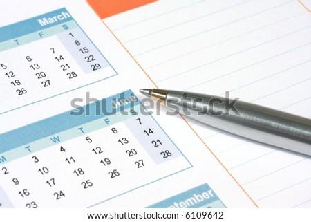 Silver and gold ballpoint pen on a calendar, with notes column.