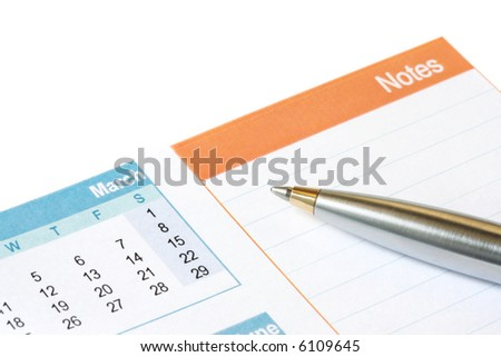 Silver and gold ballpoint pen on calendar showing space for notes.