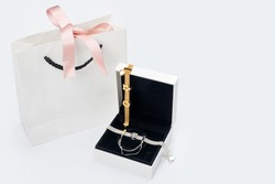Silver and gold bracelets in gift box, jewelry flatlay on neutral background. Top view of fashion luxury woman accessories, jewelry and shopping concept.
