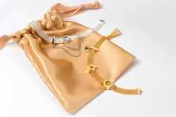 Silver and gold bracelets in golden silk gift bag, jewelry flatlay on neutral background. Top view of fashion luxury woman accessories, jewelry and shopping concept. Trendy flat lay composition.
