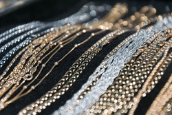 silver and gold necklaces and bracelets lying on black backgroun